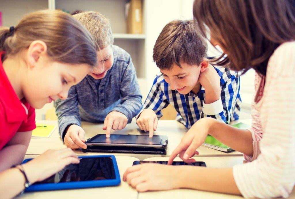 Oppilaat opiskelevat yhdessä tabletien kanssa.
