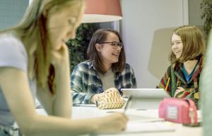 Iloiset opiskelijat opiskelevat yhdessä pöydän ääressä