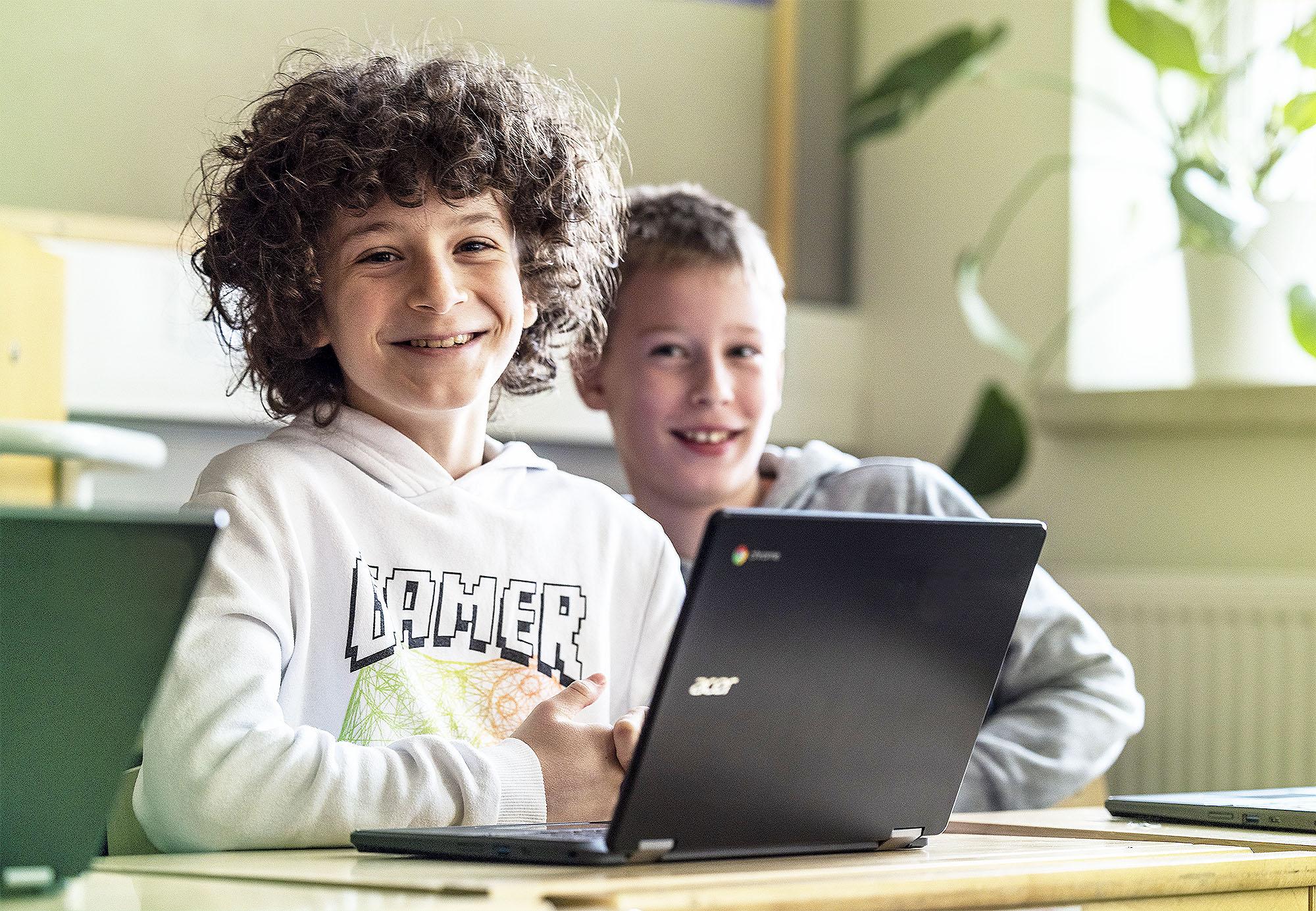 Kaksi hymyilevää poikaa opiskelee tietokoneen äärellä
