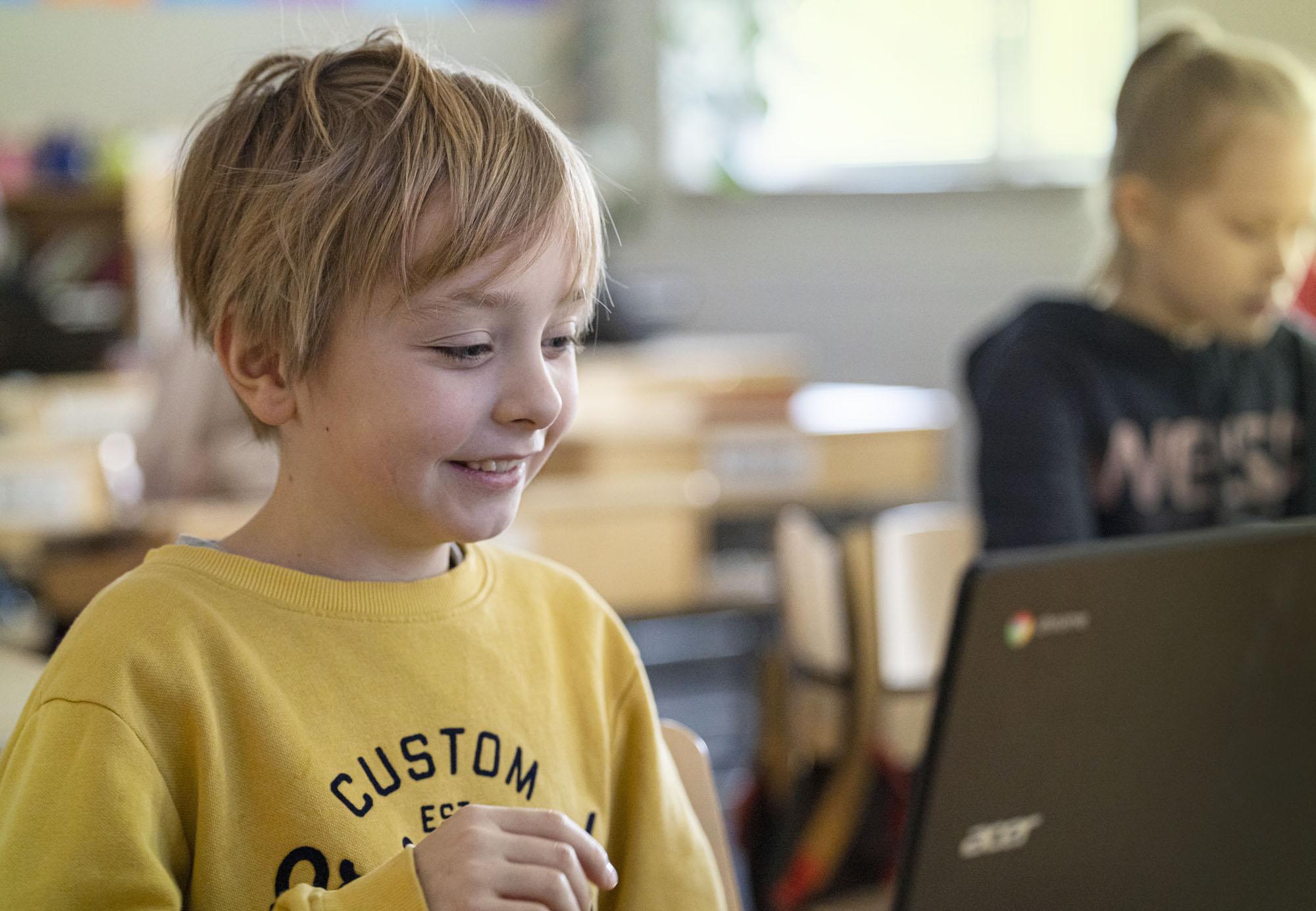 Poika opiskelee tietokoneen ääressä