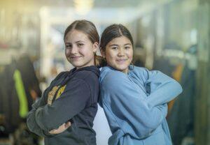 Kaksi tyttöa seisoo selät vastakkain päättäväisinä