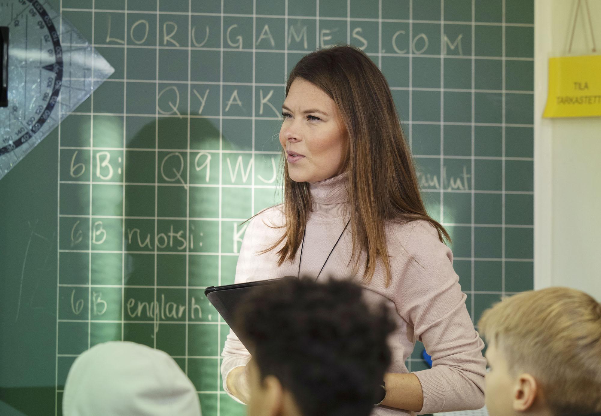 Opettaja opettaa luokan edessä