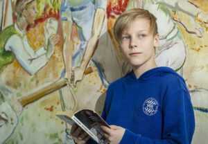 Poika lukee kirjaa nojaten koulun seinään.