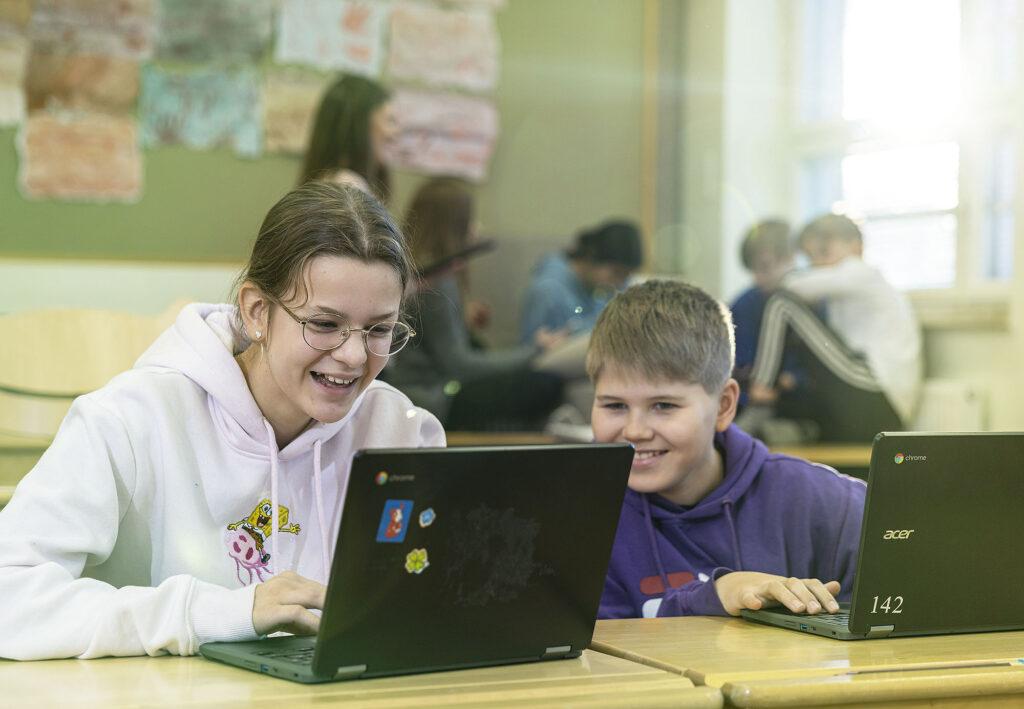 Tyttö ja poika opiskelee iloisena yhdessä tietokoneiden kanssa